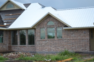 kitchen windows on right and dining windows on left; metal roofing being installed